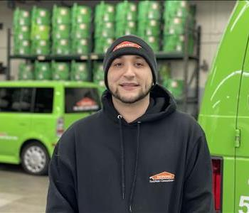 Male crew chief in front of SERVPRO vehicle