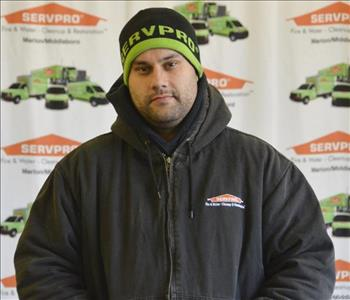 Crew Chief Josh Cunha poses in front of our SERVPRO backdrop