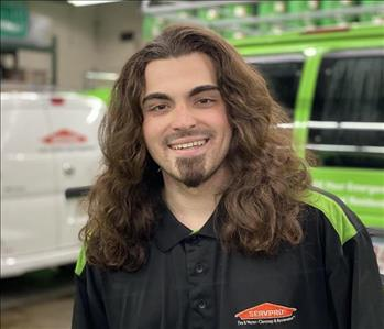 Male with brown hair in front of SERVPRO vehicles