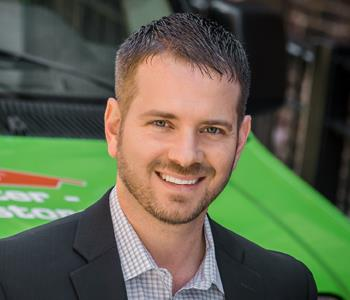 A headshot of CEO Doug Glassman in front of a SERVPRO work van